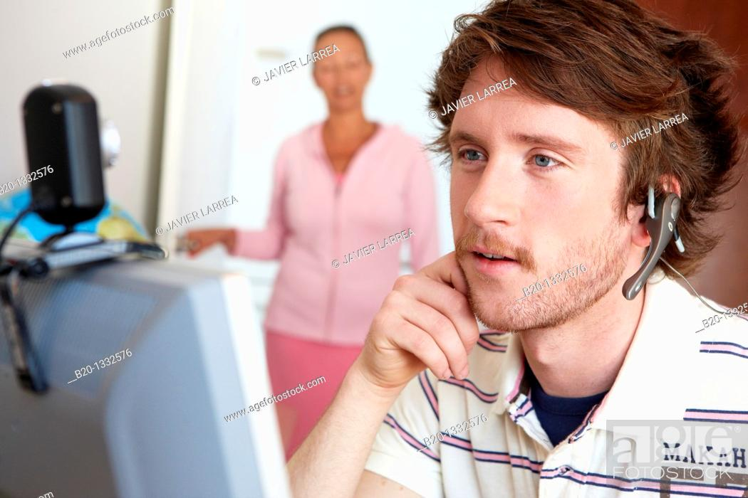 Stock Photo: Mother calling son who is looking at computer in his room.