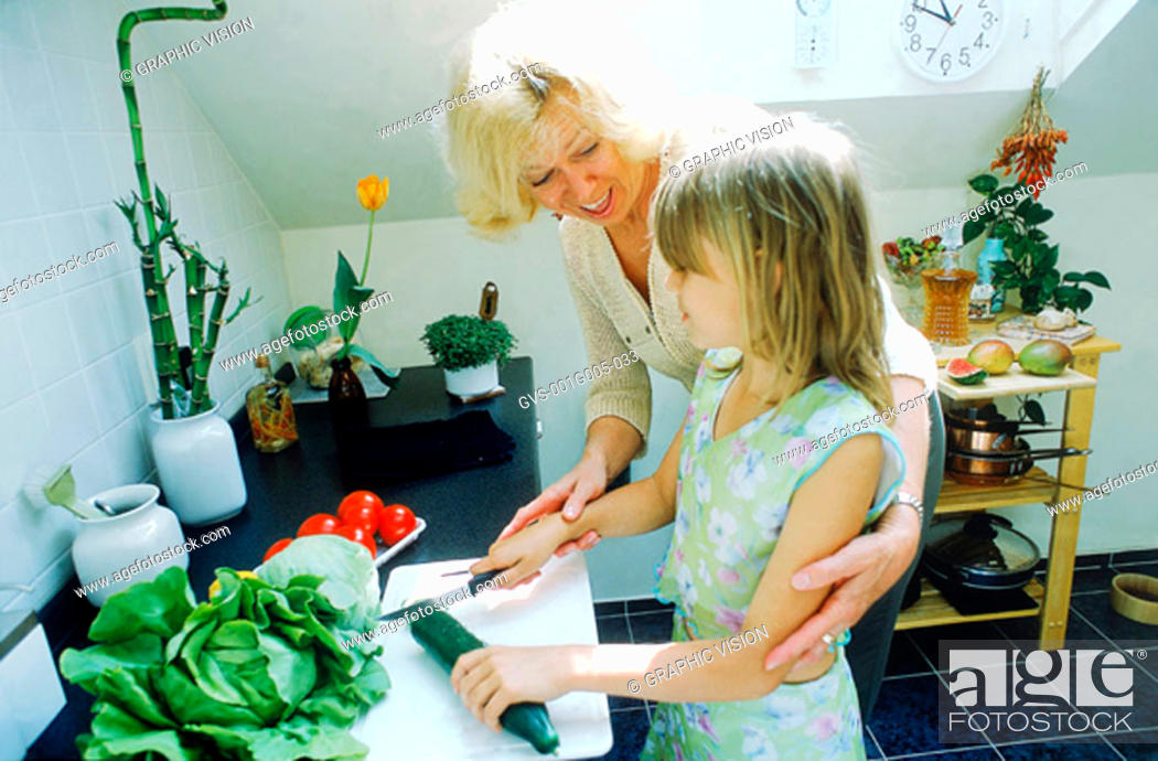 Stock Photo: Grandmother helping granddaughter in the kitchen.