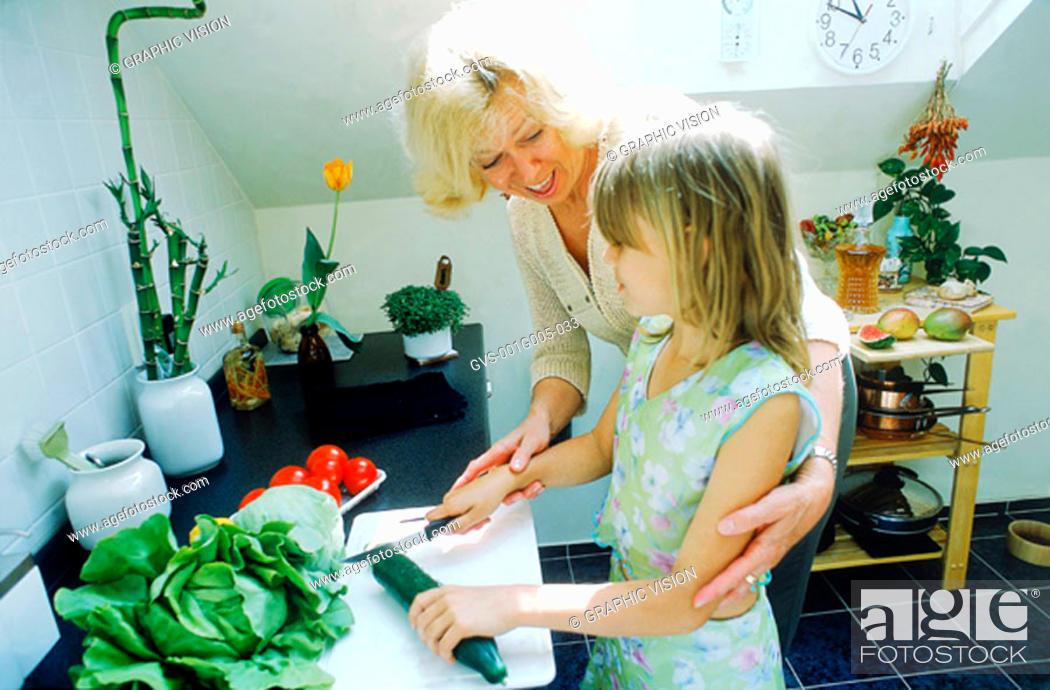 Imagen: Grandmother helping granddaughter in the kitchen.