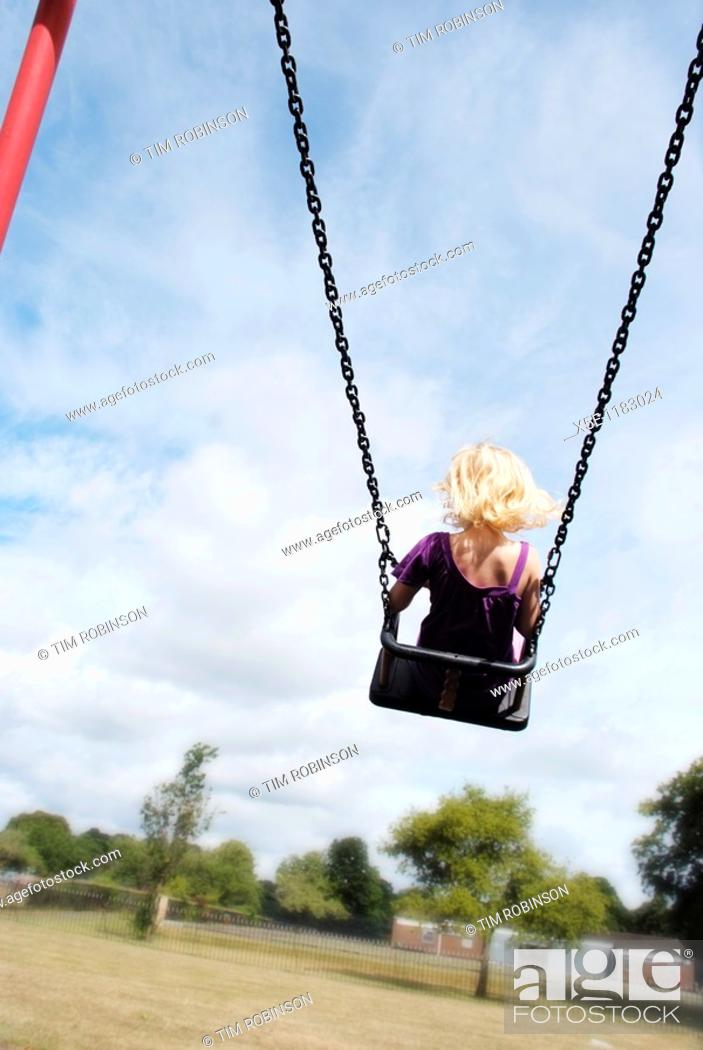 Stock Photo: Rearview 7 year girl riding high on swing in childrens playground.