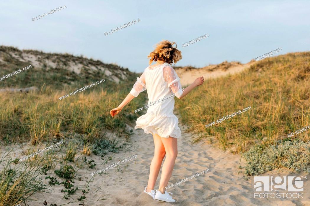 Stock Photo: Young woman in white dress dancing on coastal dunes, Menemsha, Martha's Vineyard, Massachusetts, USA.