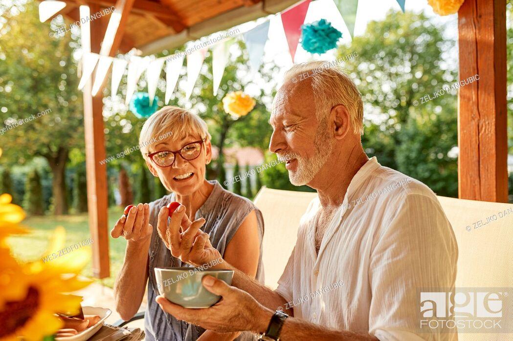 Imagen: Senior couple eating tomatoes on a garden party.