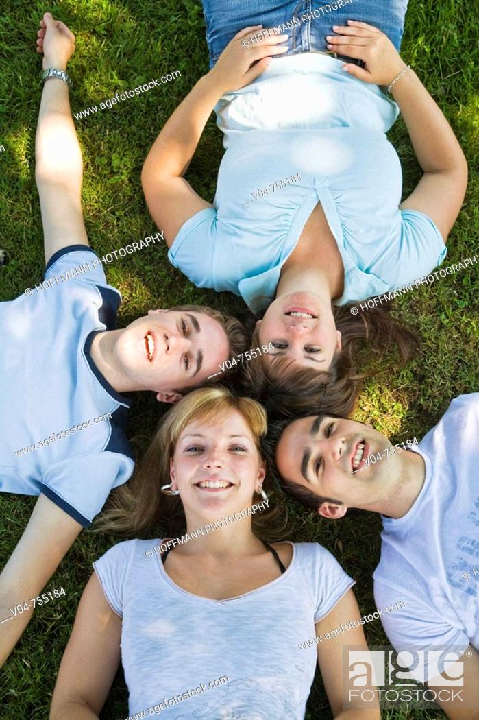 Stock Photo: Two girls and two boys lying in the grass.