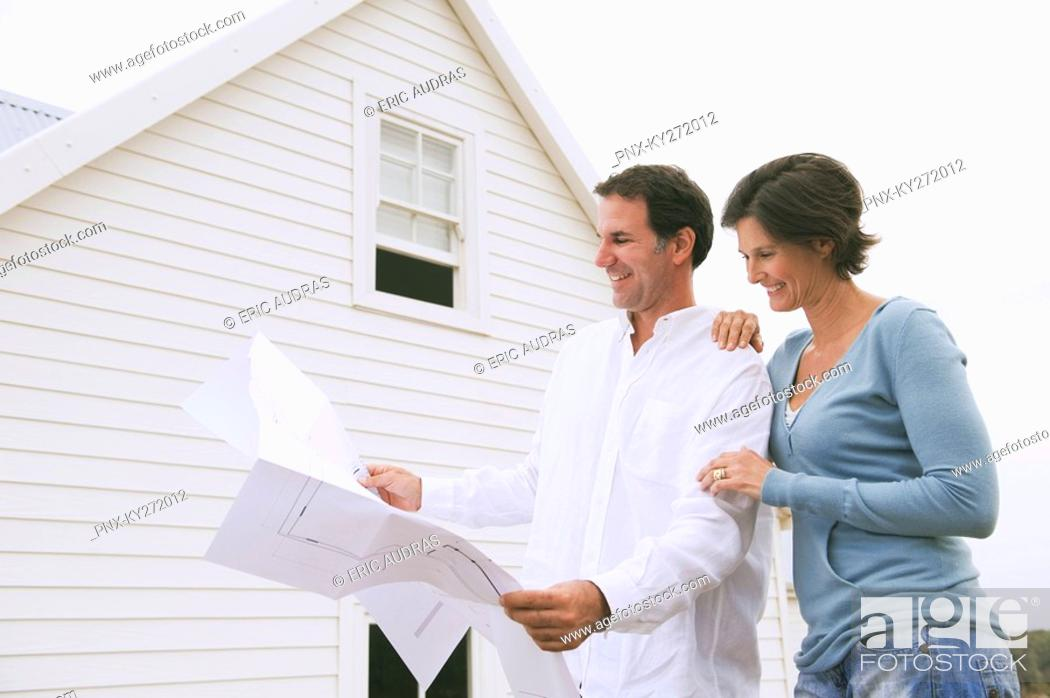 Stock Photo: Couple looking at a blueprint of a house.