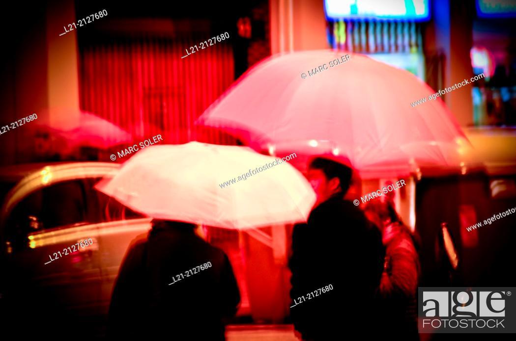 Stock Photo: People with umbrellas. Rainy day, night. Barcelona, Catalonia, Spain.