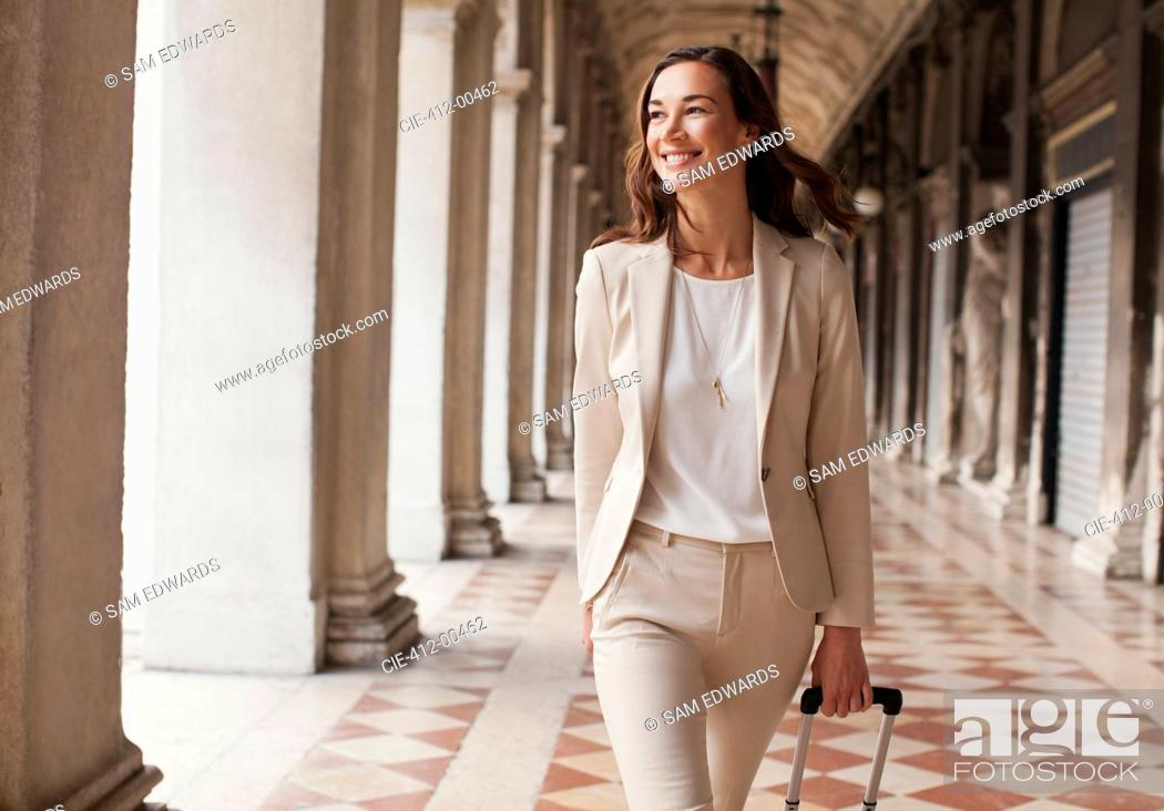 Stock Photo: Confident businesswoman pulling suitcase along corridor.