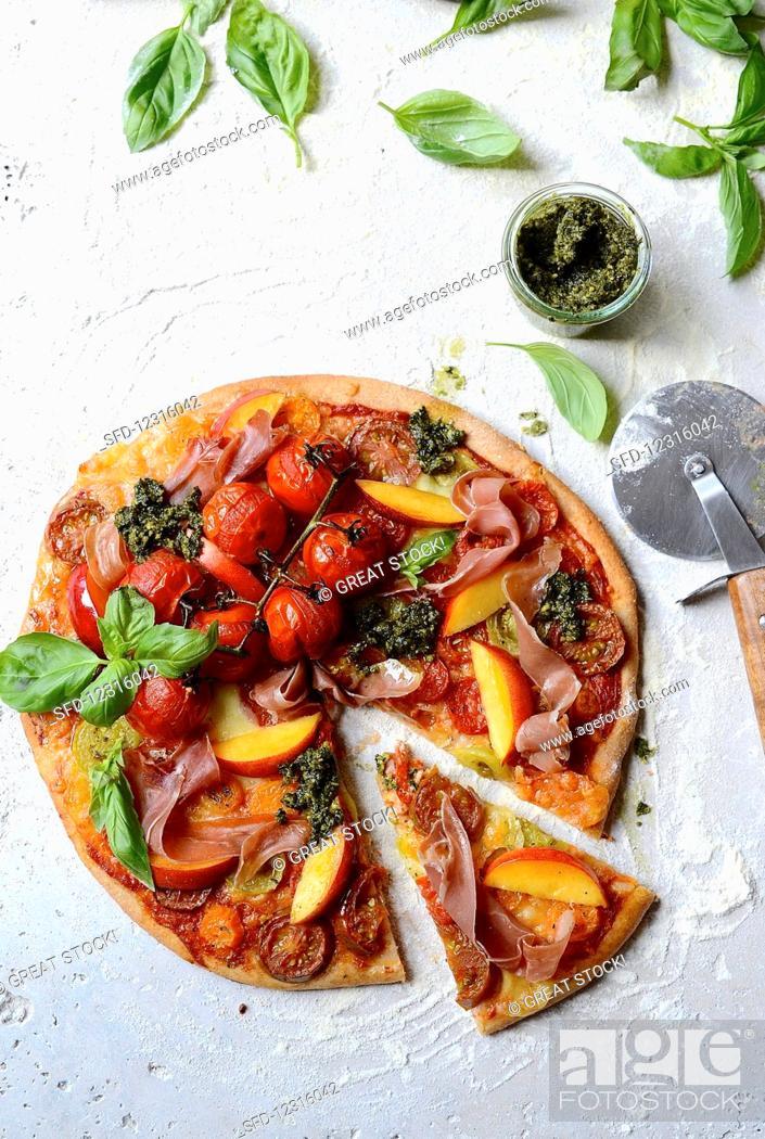 Photo de stock: Spelt pizza with tomatoes, ham, nectarines and kale pesto.