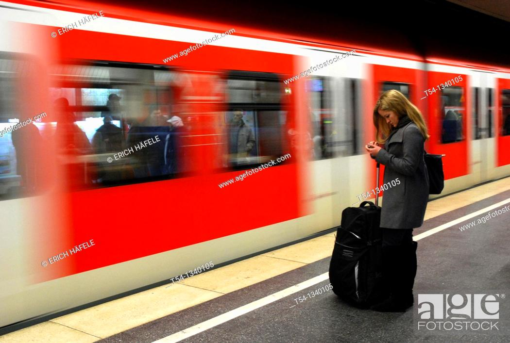 Stock Photo: A young woman with luggage, SMS reads as the train enters into the Metro station.