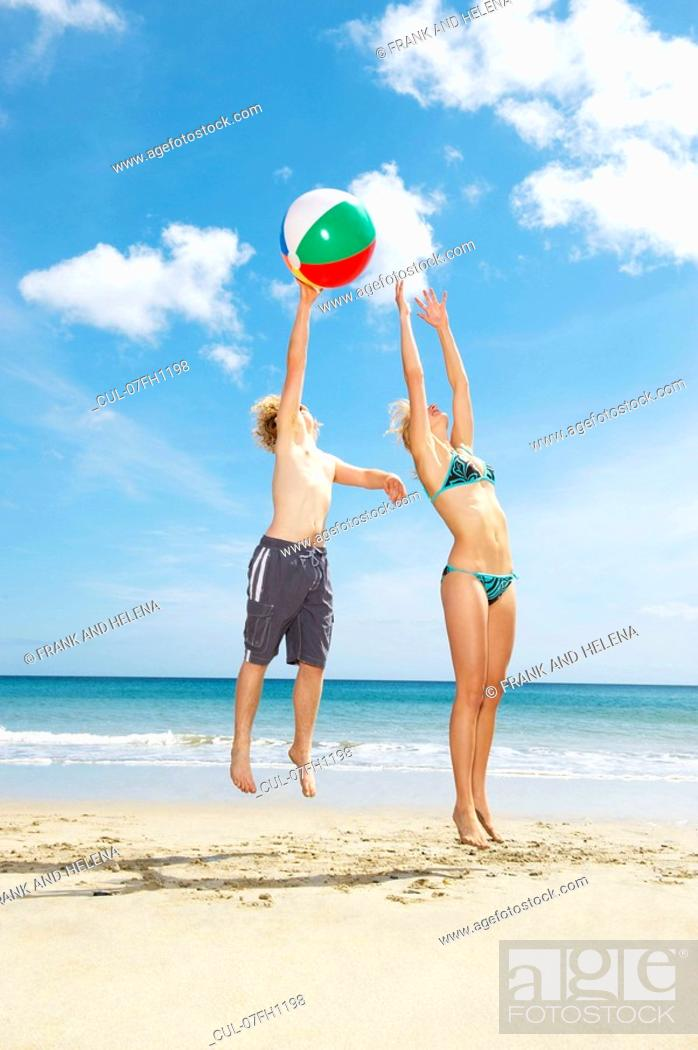 Stock Photo: Young couple leaping for beach ball.