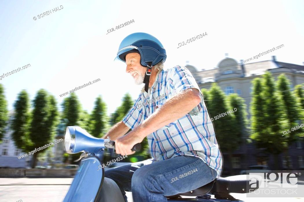 Stock Photo: Man on scooter.