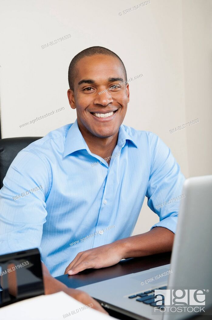 Stock Photo: Smiling African American businessman sitting at desk.