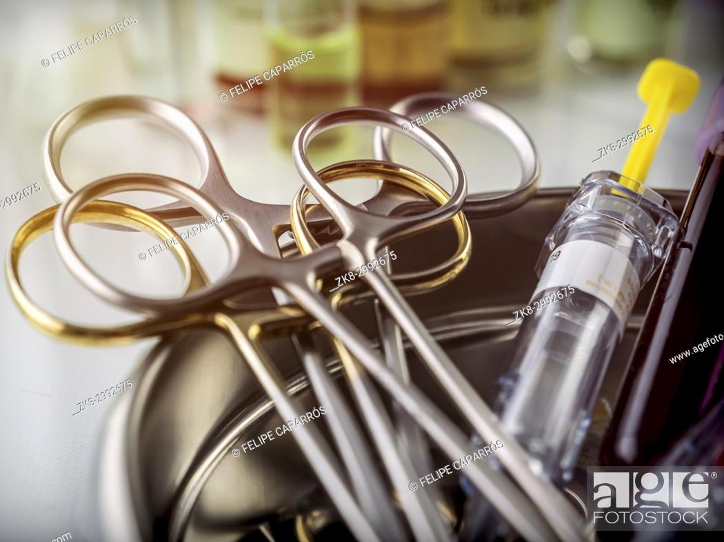 Stock Photo: Scissors and vials of blood samples in a tray on a table of a hospital, conceptual image.