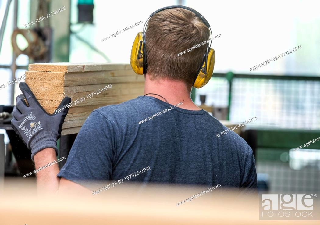 Stock Photo: 24 July 2019, Mecklenburg-Western Pomerania, Wismar: An employee places wooden boards for the production of new wooden pallets at the company Paletten-Service.