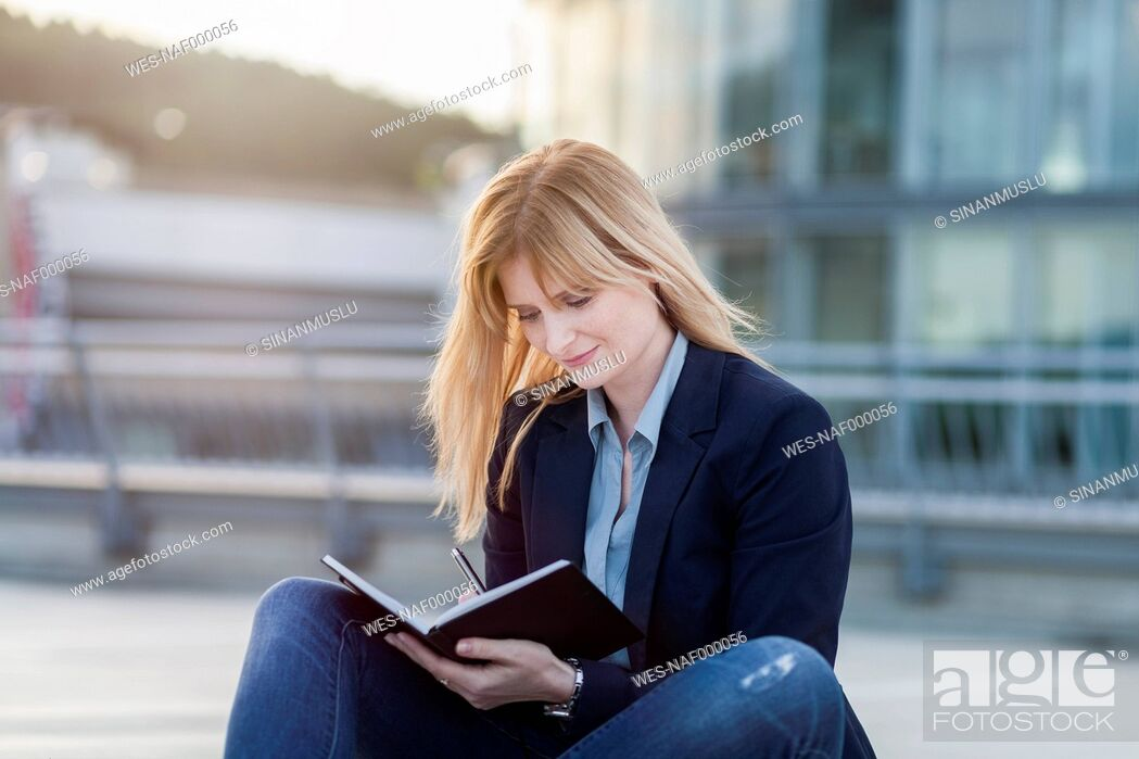 Stock Photo: Businesswoman with notebook writing down something.
