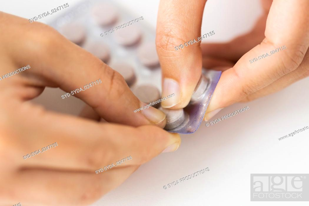Stock Photo: woman hands opening pack of medicine pills.