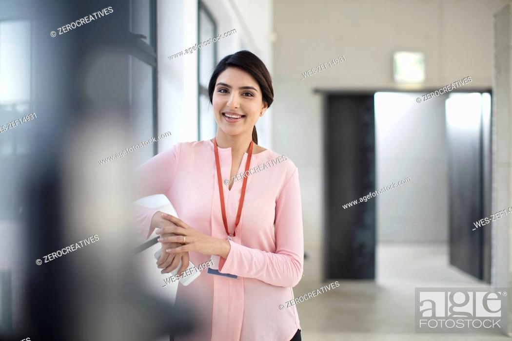 Stock Photo: Portrait of smiling young woman standing on the corridor in office.
