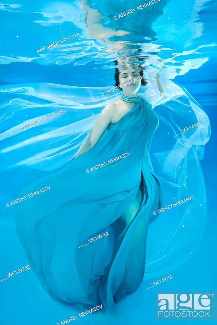 Stock Photo: beautiful woman in a long dress posing under water.