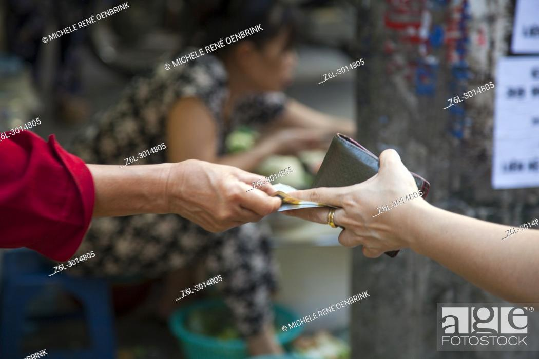 Stock Photo: Paying for food at the street market in Hanoi, Vietnam.