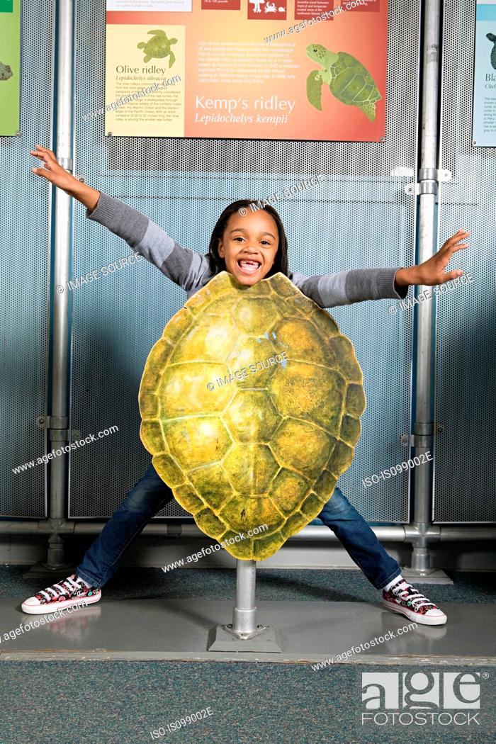 Stock Photo: Girl standing behind kemps ridley sea turtle shell.