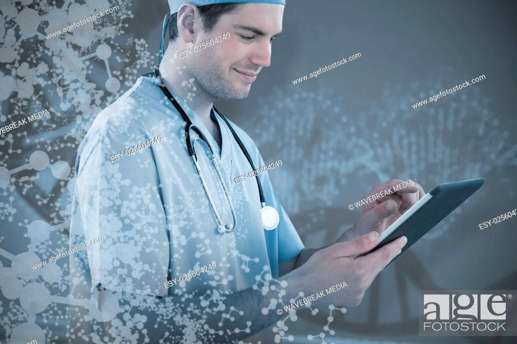 Stock Photo: Composite image of surgeon using digital tablet.
