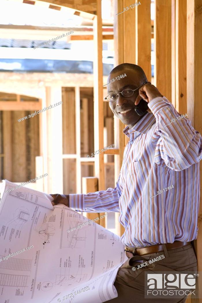 Stock Photo: Businessman with blueprint in partially built house, using mobile phone, portrait.