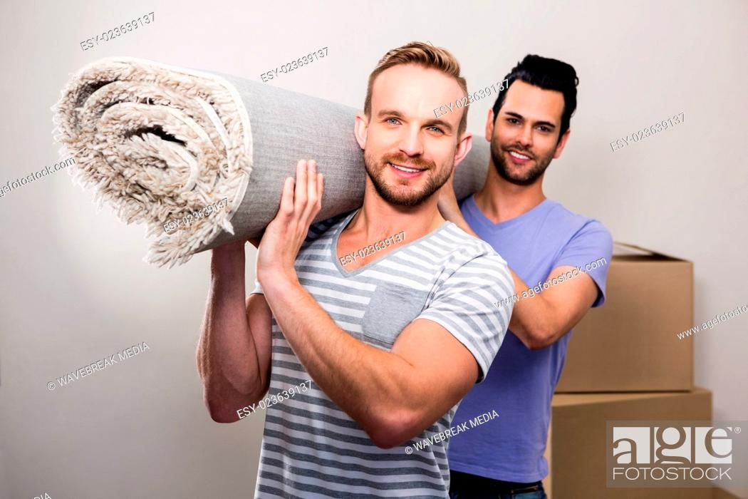 Stock Photo: Gay couple carrying rolled up carpet.