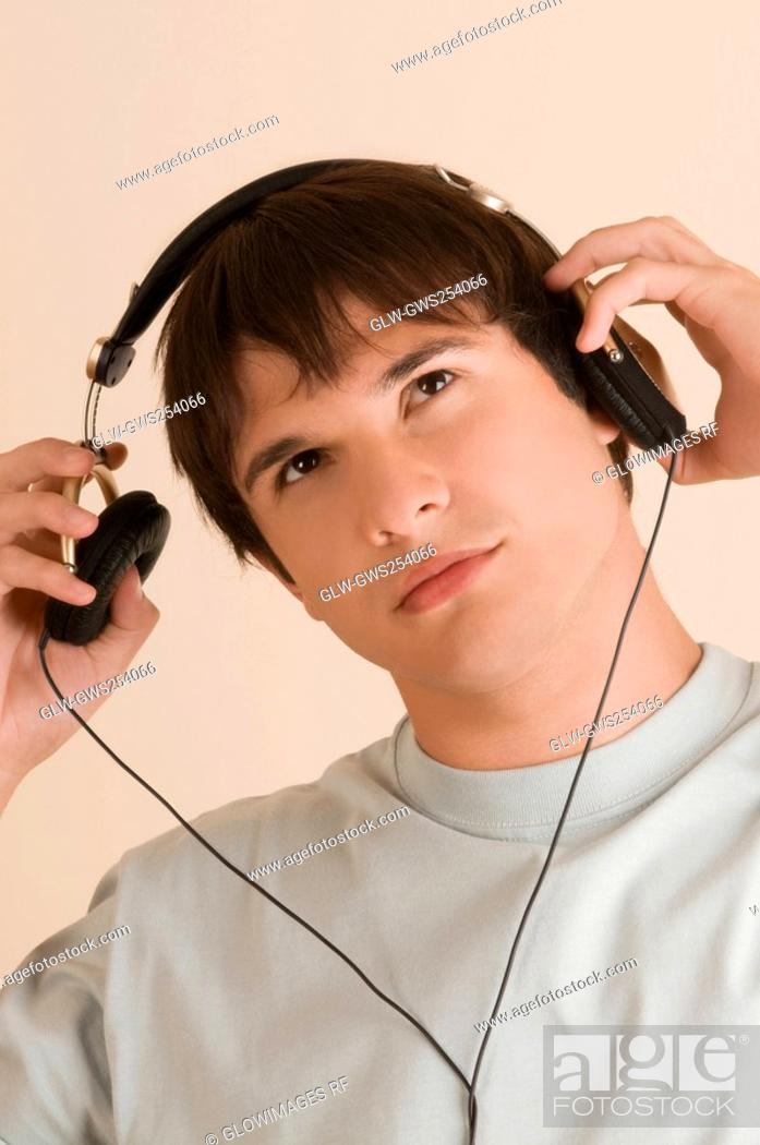 Stock Photo: Close-up of a young man listening to music.