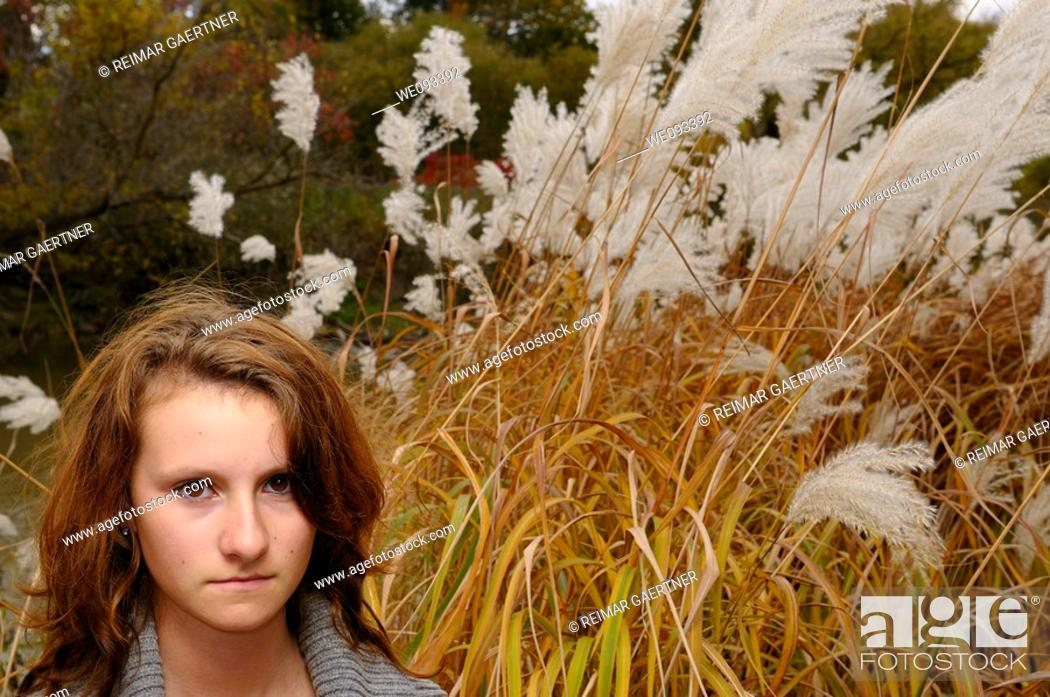 Stock Photo: Young girl standing by a river in the Fall with tall wild white plumed Pampas Grass.