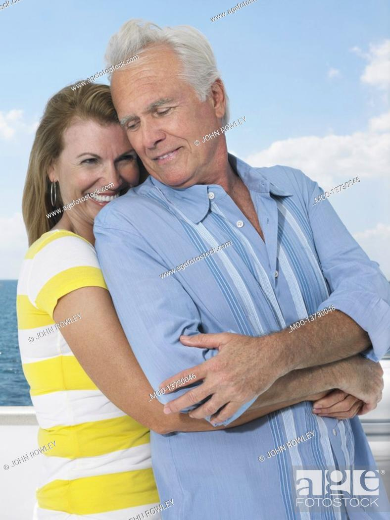 Stock Photo: Middle-aged couple embracing on yacht.