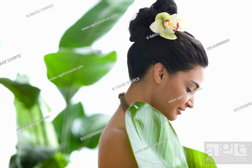 Stock Photo: Young woman holding a large leaf.
