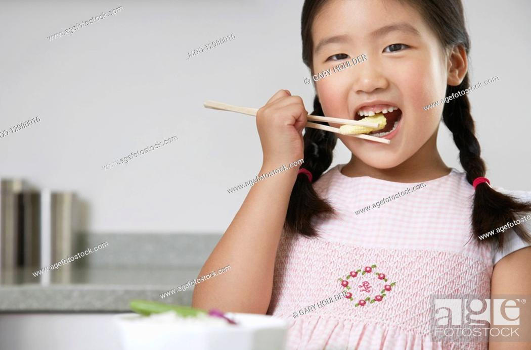 Stock Photo: Young Girl with pigtails Eating Baby Corn with chopsticks.