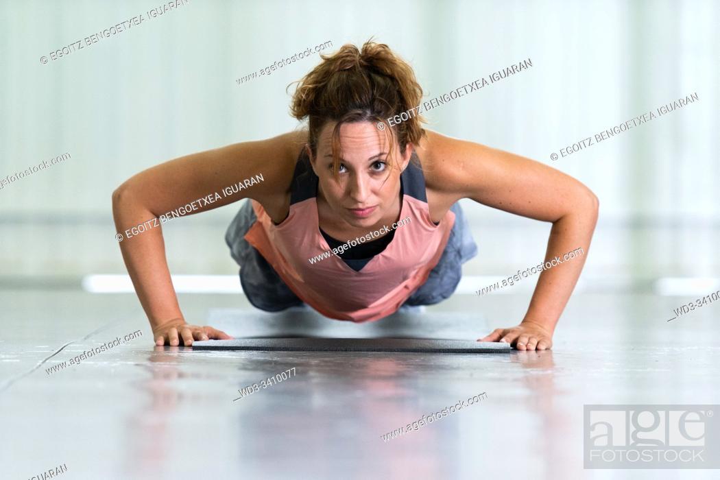 Stock Photo: Young woman making push-ups.
