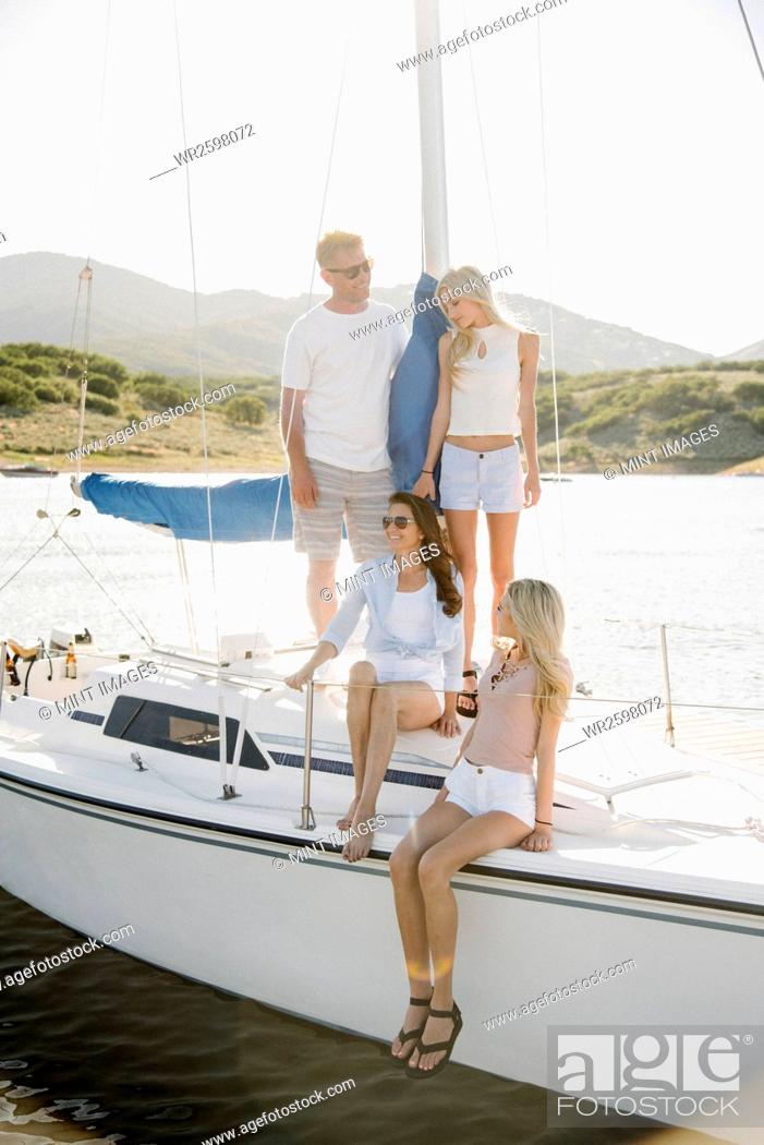 Imagen: Man, woman and their two blond daughters on a sail boat.
