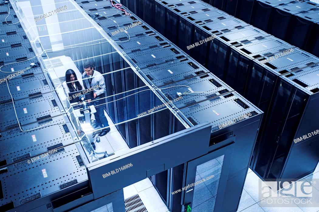 Stock Photo: High angle view of technicians working in server room.