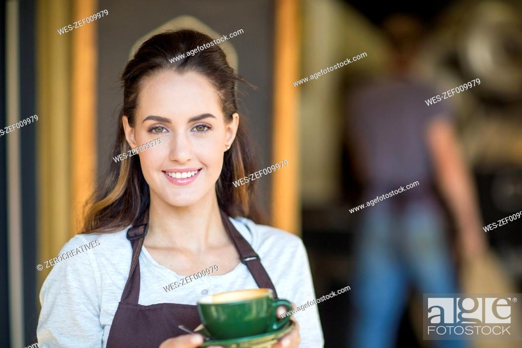 Stock Photo: Portrait of smiling young woman holding cup of coffee.