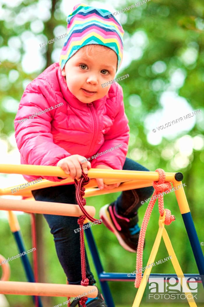 Stock Photo: The little baby girl playing at outdoor playground against green grass at autumn.