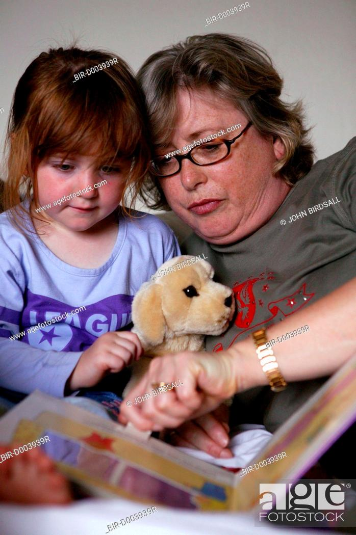 Stock Photo: Young girl looking at a book with her Grandmother,.
