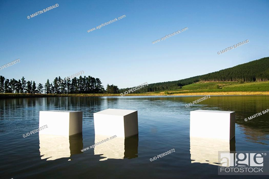 Stock Photo: Boxes floating in water with trees.
