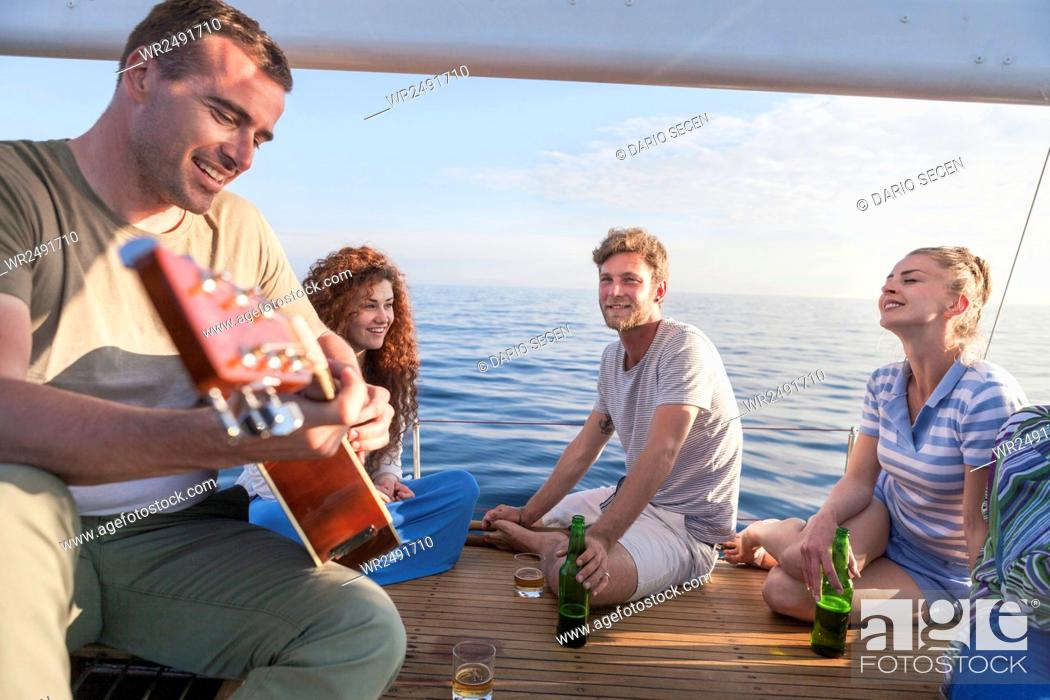 Imagen: Young man playing guitar on sailboat with friends listening.