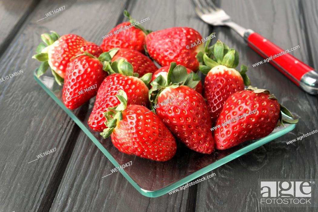 Photo de stock: bunch of ripe strawberries on modern black board.