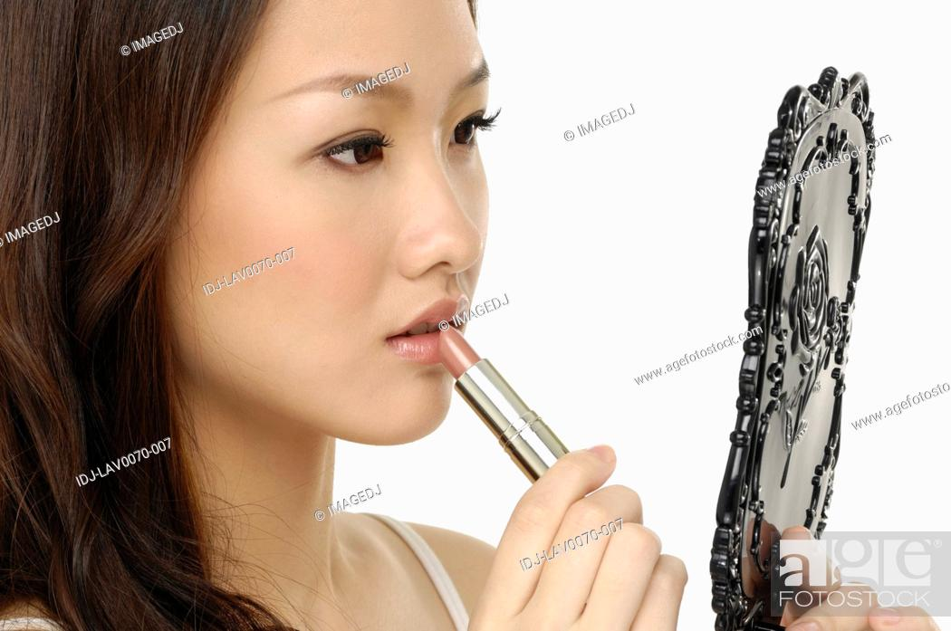 Stock Photo: Smiling woman applying gloss isolated on a white background.