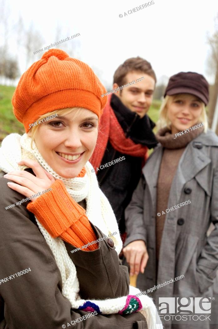Stock Photo: Close-up of a young woman smiling with her friends standing in the background.
