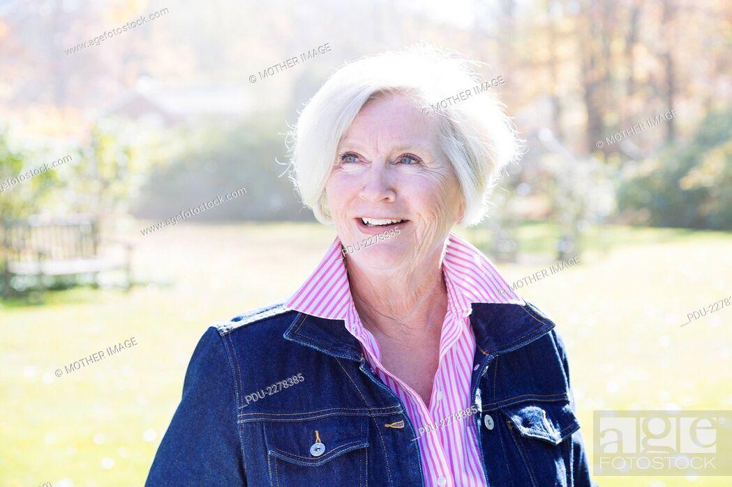 Stock Photo: Fashionable Senior woman smiles off camera outside.