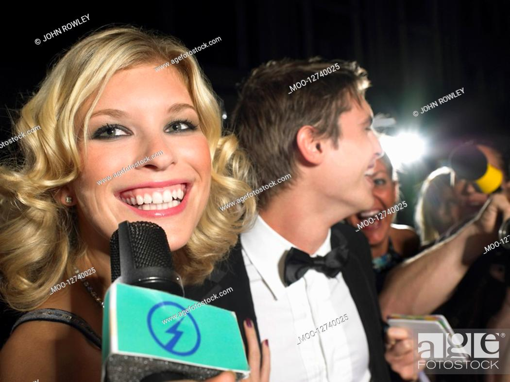 Stock Photo: Woman talking into microphone man behind with paparazzi.