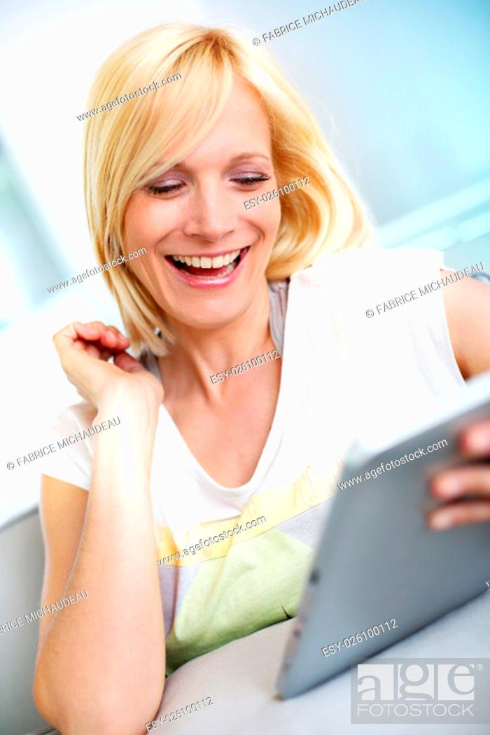 Stock Photo: Smiling blond girl looking at tablet screen.