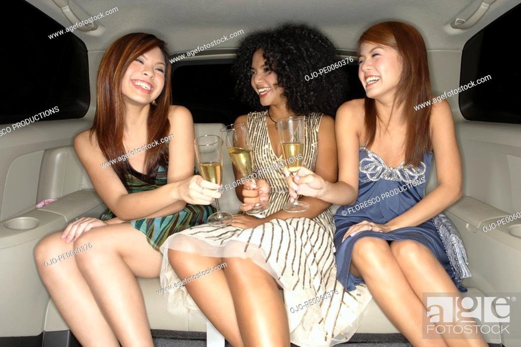 Stock Photo: Three women in limousine toasting champagne flutes laughing.