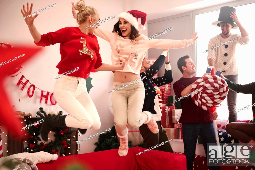 Stock Photo: Young women jumping on sofa at christmas party.