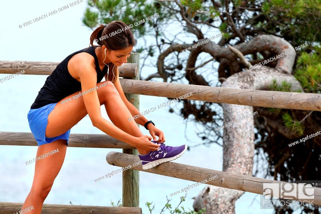 Stock Photo: Runner tying laces on wooden fence.