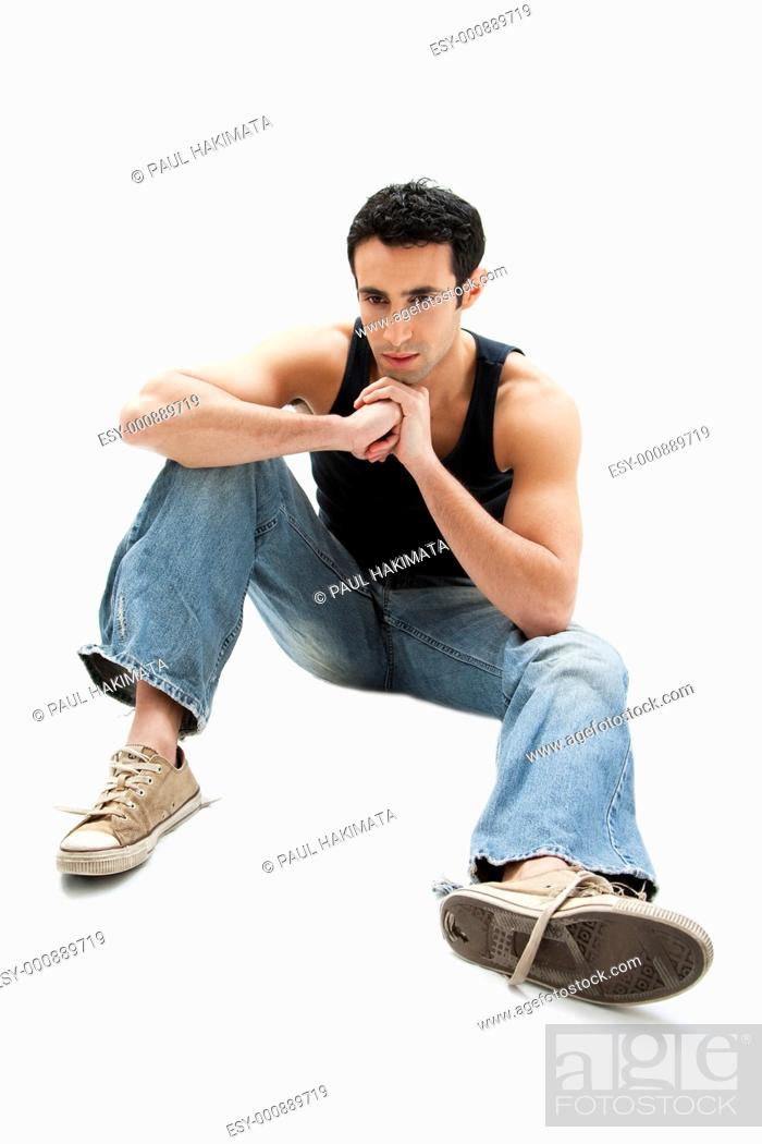 Stock Photo: Handsome Caucasian guy wearing black tank top and jeans sitting on floor thinking, isolated.