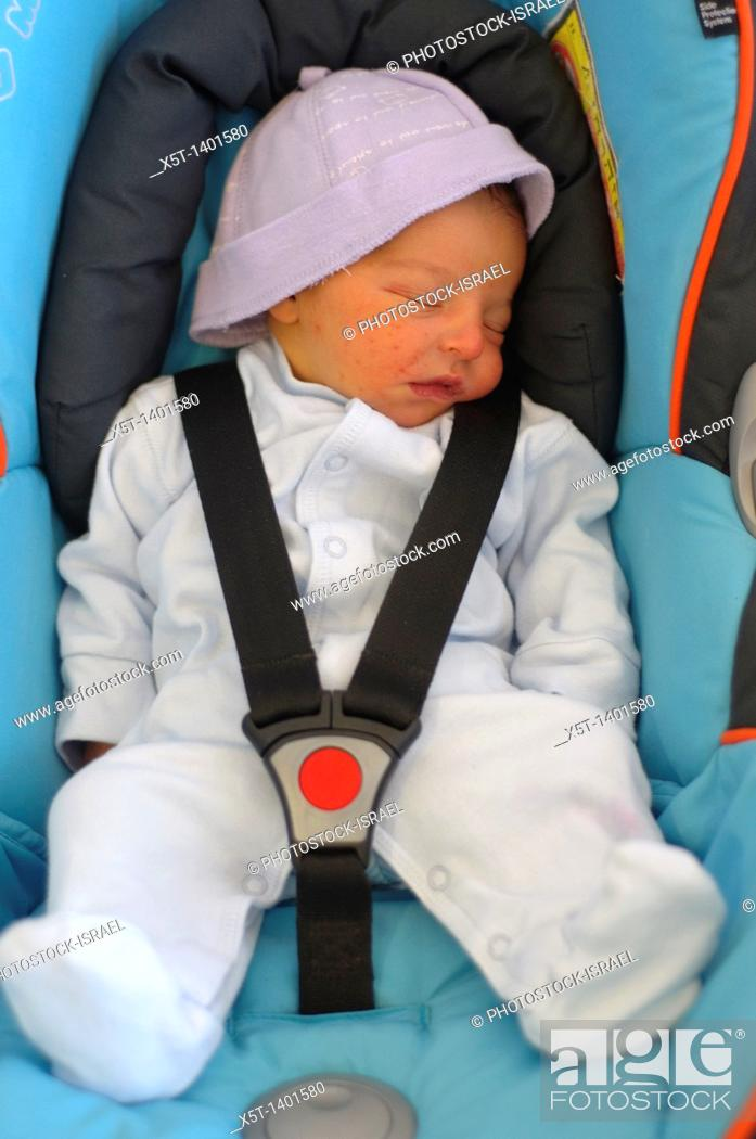 Stock Photo: Baby boy sleeping strapped into a car seat.